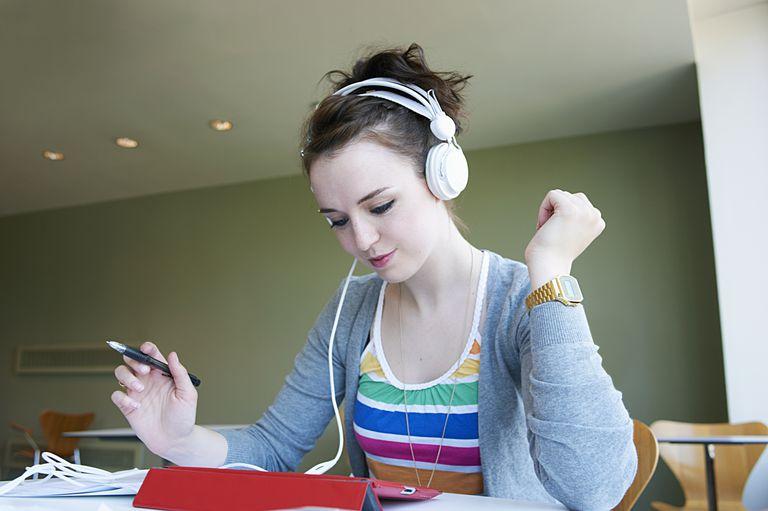 Девушка слушает музыку и зарабатывает на размещении статей
